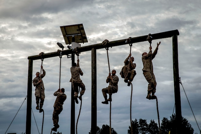 Six Marines climb ropes tied to a wooden structure outside.
