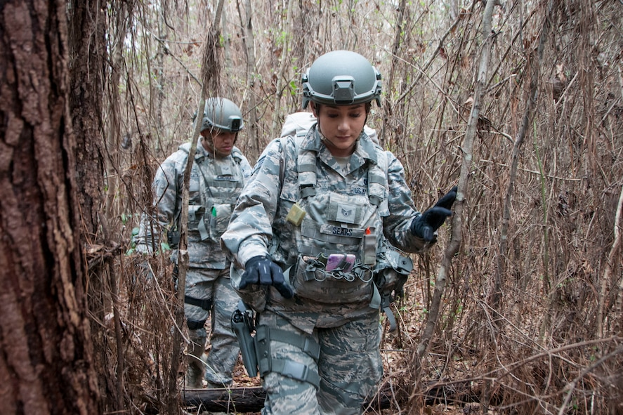 Staff Sgt. Sashalynn Sears (center) and Airman 1st Class Juanito Gacusan, 154th Security Forces Squadron fireteam member, searches the forest as part simulated search and rescue sweep as part of Patriot South Feb. 14, 2018, at Camp Shelby, Mississippi.