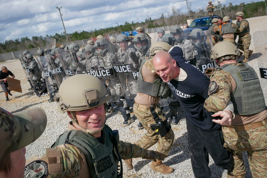 Members of the Mississippi Department of Wildlife, Fisheries and Parks Special Response Team apprehend Master Sgt. Joshua Go Forth, 129th Security Forces Squadron squad leader, during a training exercise Feb. 15, 2018, at Camp Shelby, Mississippi.