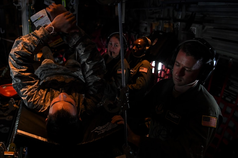 (Right) U.S. Air Force Staff Sgt. David Francis, 349th Aeromedical Evacuation Squadron technician, treats a simulated patient during an aeromedical mission over Rota, U.S. Commonwealth of the Northern Mariana Islands, during exercise COPE NORTH 18, Feb. 19.