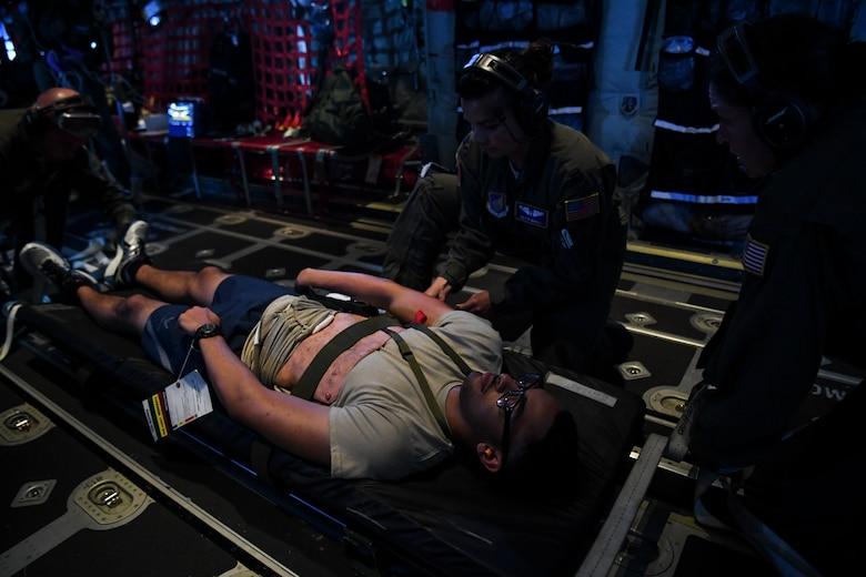 (Right) U.S. Air Force Major Catherine Paterson, 439th Aeromedical Evacuation Squadron, and Captain   Betsy Mayes, 349th Aeromedical Evacuation Squadron flight nurse, treat a simulated patient during an aeromedical mission over Rota, U.S. Commonwealth of the Northern Mariana Islands, during exercise COPE NORTH 18, Feb. 19.