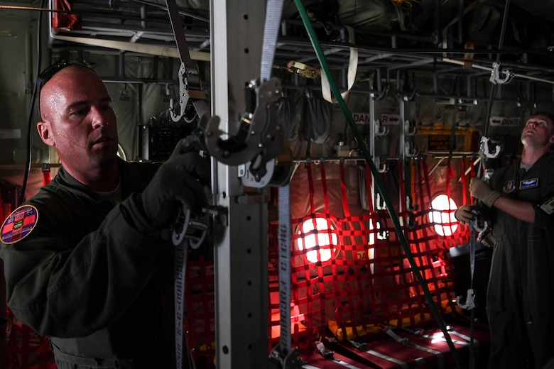 (Left) U.S. Air Force Master Sgt. Ryan McClellan, 36th Aeromedical Evacuation Squadron technician, and Staff Sgt. David Francis, 349th Aeromedical Evacuation Squadron technician, configure the inside of a U.S. Air Force C-130J Super Hercules for an aeromedical mission at Andersen Air Force Base, Guam, during exercise COPE NORTH 18, Feb. 19.