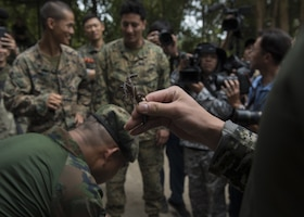Marines get ready to eat a scorpion.