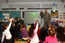 Col. Joseph A. Muhlbauer, the chief of dental professional staff assigned to the 48th Dental Squadron, interacts with children at Lakenheath Elementary School at Royal Air Force Lakenheath, England, Feb. 20, 2018. Muhlbauer shared fun stories of the dental clinic to facilitate positive reactions to the idea of dental visits. (U.S. Air Force photo/Airman 1st Class Shanice Williams-Jones)