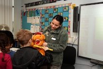 Airman Mariah M. Perez, a dental technician assigned to the 48th Dental Squadron, holds a stuffed animal, and teaching aide, at the Lakenheath Elementary School at Royal Air Force Lakenheath, England, Feb. 20, 2018. National Children's Dental Health Month aims to raise awareness and promote the benefits of good oral hygiene to children. (U.S. Air Force photo/Airman 1st Class Shanice Williams-Jones)