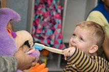 A child brushes the teeth of a stuffed animal at the Child Development Center at Royal Air Force Lakenheath, England, Feb. 13, 2018. Every child was encouraged to brush the toy's teeth to raise awareness of good oral hygiene for the 2018 National Children's Dental Health Month. (U.S. Air Force photo by Airman 1st Class Shanice Williams-Jones)