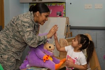 Airman 1st Class Tanisha T. Forbes, a dental technician assigned to the 48th Dental Squadron, gives a child a high-five at the Child Development Center at Royal Air Force Lakenheath, England, Feb. 13, 2018. Forbes used encouraging words and questions to engage the children during a dental health presentation. (U.S. Air Force photo/Airman 1st Class Shanice Williams-Jones)