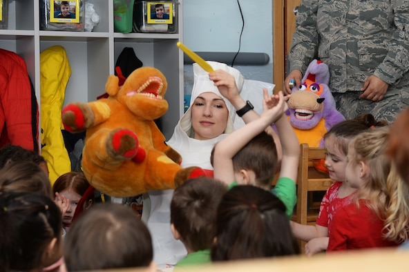 Capt. Candice V. Hodges, a general dentist assigned to the 48th Dental Squadron, raises a stuffed animal and toothbrush for children to see at the Child Development Center at Royal Air Force Lakenheath, England, Feb. 13, 2018. Hodges wore a toothpaste costume in the spirit of promoting good oral hygiene. (U.S. Air Force photo/Airman 1st Class Shanice Williams-Jones)