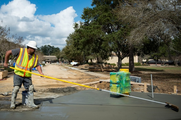 Juan Zaragoza, construction concrete finisher, smooths out cement during the reconstruction of Mitchell Gate, Feb. 21, 2018, at Moody Air Force Base, Ga. The 23d Civil Engineer Squadron partnered with civilian contractors to reconstruct the gate in an effort to improve the security posture with improved anti-terrorism force protection barriers. (U.S. Air Force photo by Airman 1st Class Erick Requadt)