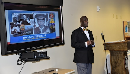 Gene Quinton, secretary for the Director for Administration, Naval Health Clinic Charleston, highlights the military career of his cousin, Lt. Gen. Frank Petersen, Jr., the first black pilot and general in the Marine Corps, during NHCC's Black History Month observance Feb. 16 at the clinic. NHCC staff members celebrated the many contributions and accomplishments of black Americans during the annual event.