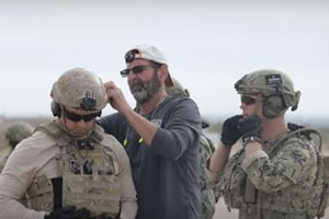 A man attaches a device to a service member's helmet.