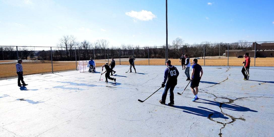 Members of Team Whiteman participate in the first extramural hockey practice at Whiteman Air Force Base, Mo., Feb. 17, 2018. The old skate park outside the fitness center provides the teams enough space to practice techniques and play games. (U.S. Air Force photo by Staff Sgt. Danielle Quilla)