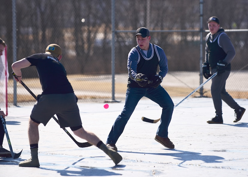 Members of Team Whiteman attempt to take control of the ball for their team in the first extramural hockey practice at Whiteman Air Force Base, Mo., Feb. 17, 2018. The teams were open to anyone who was interested in testing out their hockey skills or wanting learn more about street hockey in general. (U.S. Air Force photo by Staff Sgt. Danielle Quilla)