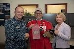 Capt. Ginnane and Brenda Minnema present Brian Lewer, with an OSU grab bag.