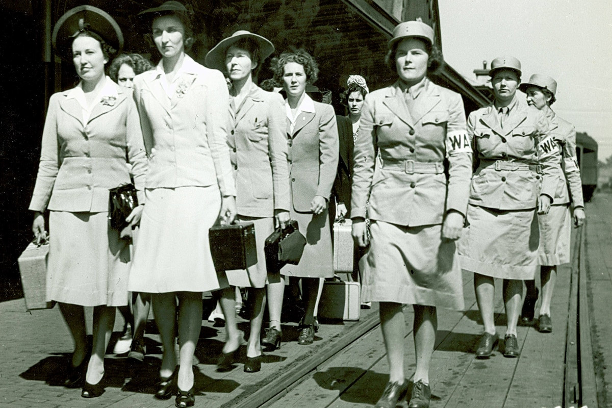 In a historic photo, Women's Army Auxiliary Corps members walk near railroad tracks.