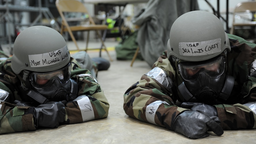 Two males wait on a concrete floor during an exercise wearing helmets.