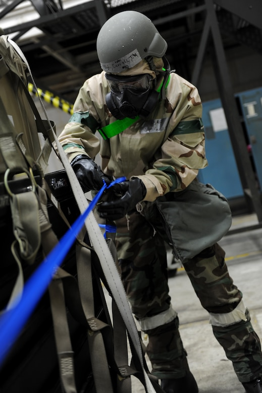 A male pulls a piece of blue tape over a pallet.