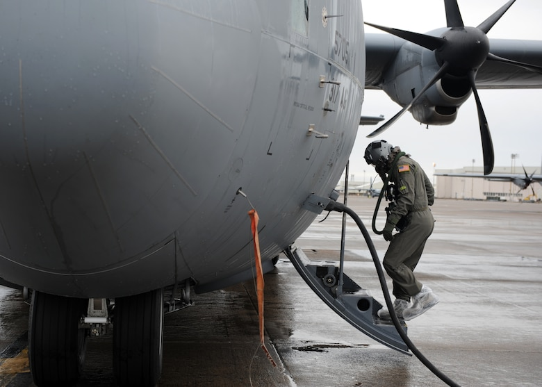 A male boards a grey C-130J.