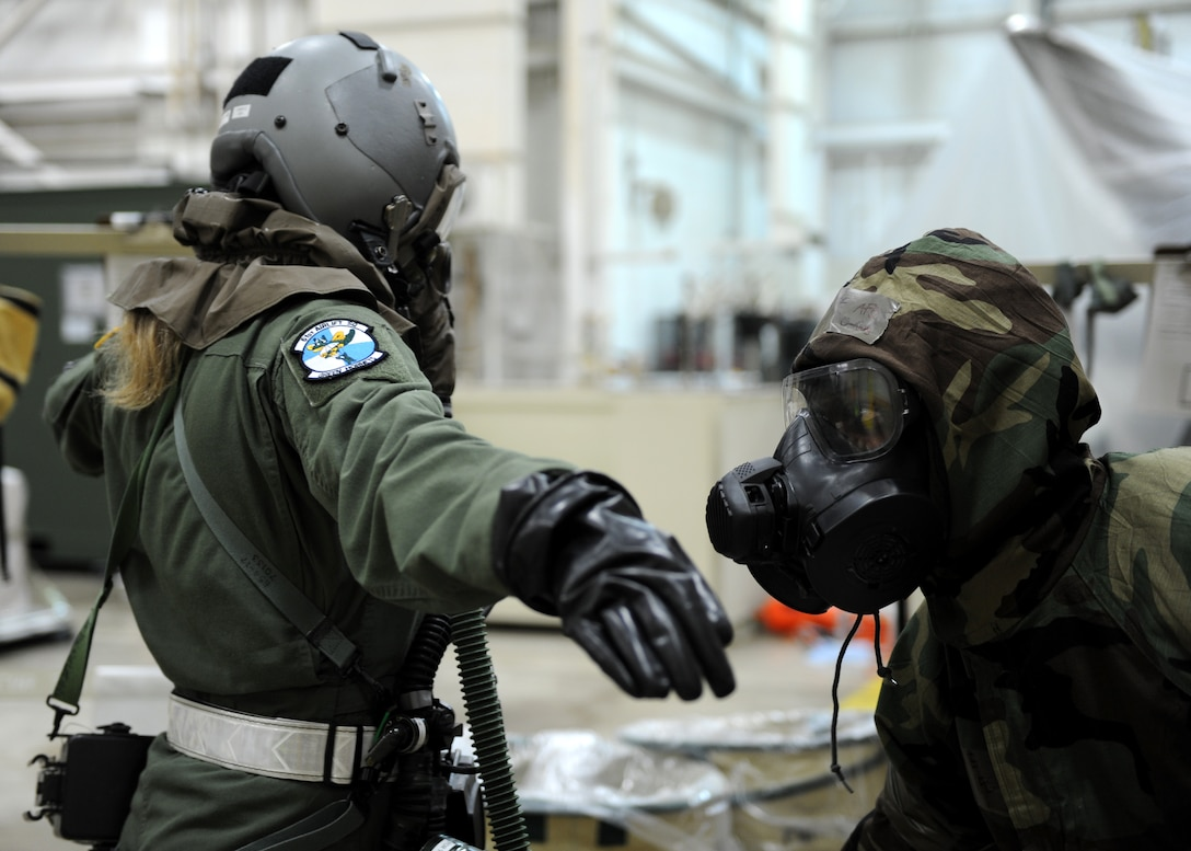 A male assists a female with a mock decontamination process.