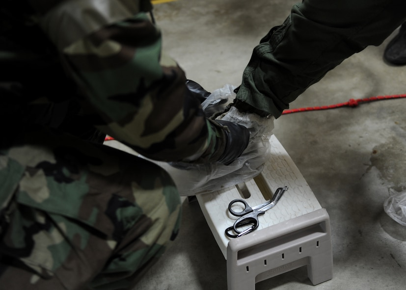 A photo with a male removing a clear plastic cover from a green combat boot.