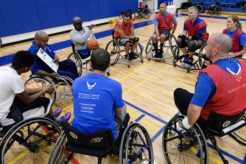 Men in wheelchairs on a basketball court sit around a man in a wheelchair holding a basketball.