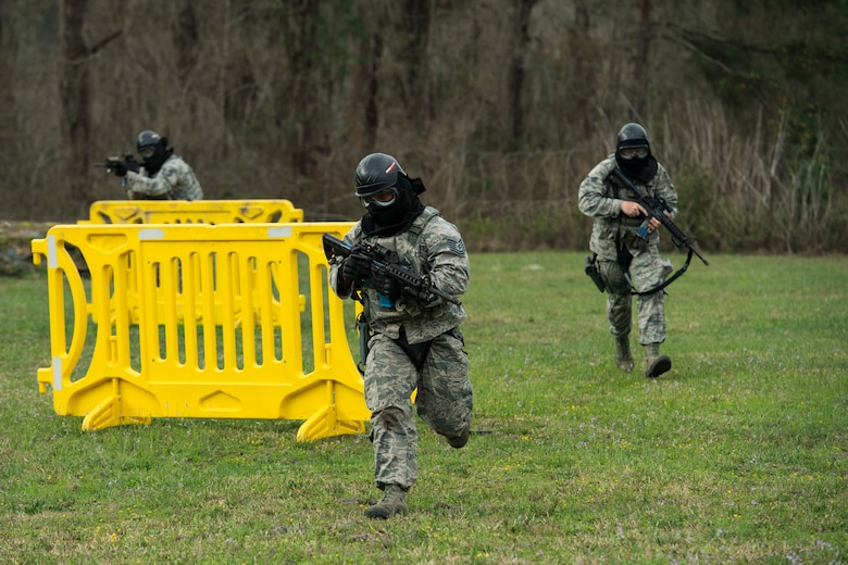"""Shoot, move, communicate"" is a training event that tests participants on their ability to move from barricade to barricade as a team. While one member provided covering fire the others advanced on the enemy, then retreated from the scenario while they maintained cover fire. Security Forces members would employ these tactics anytime they're under enemy fire. (U.S. Air Force photo by Senior Airman Janiqua P. Robinson)"