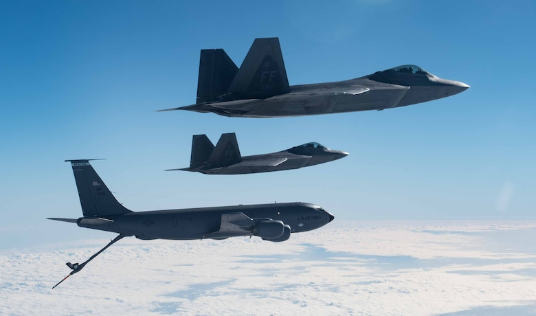 A KC-135 Stratotanker from the 101st Air Refueling Wing flies in formation with F-22 Raptors from the 94th Fighter Squadron over the Atlantic Ocean, February 22, 2018.
