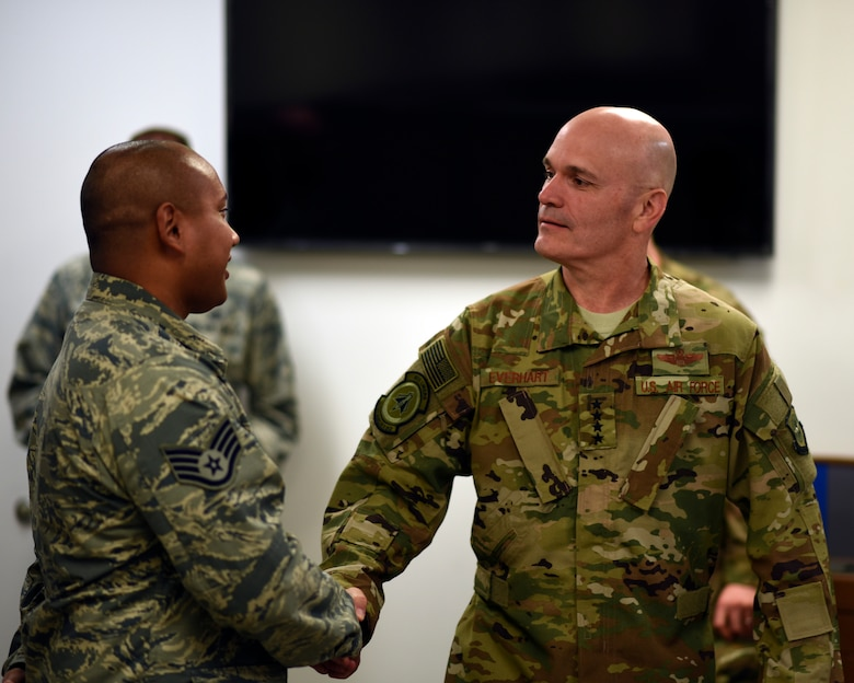 Gen shakes Airman's hand