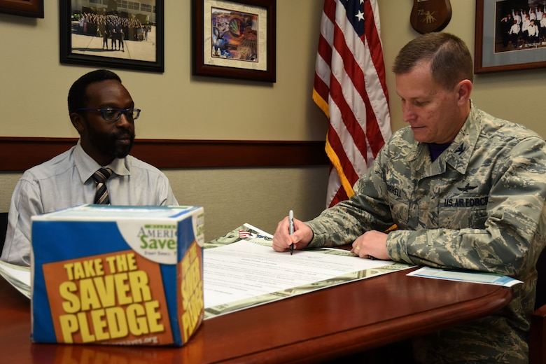 Financial Readiness manager, William Gathecha and U.S. Air Force Col. Jeffrey Sorrell, 17th Training Wing vice commander, sign a proclamation kicking off the Military Saves Week at the Norma Brown building on Goodfellow Air Force Base, Texas, on Feb. 23, 2018. The Airman and Family Readiness center has classes and seminars coordinated around setting up a savings plan for service members, civilians and their families Feb. 26 through March 3. (U.S. Air Force photo by Airman 1st Class Seraiah Hines/Released)