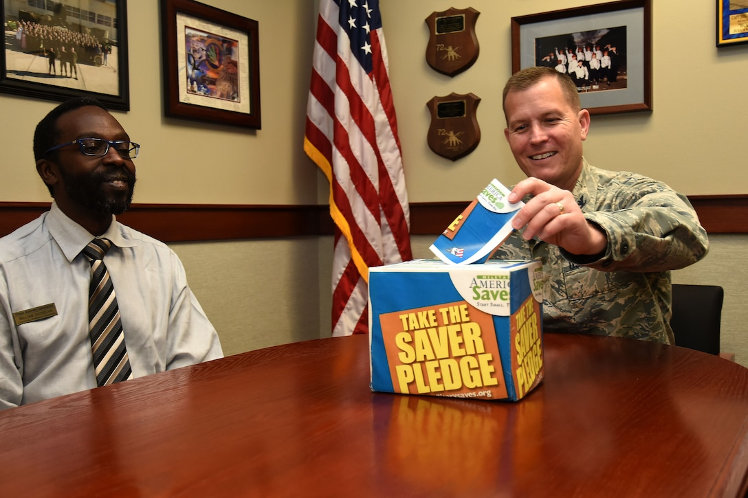 Financial Readiness manager, William Gathecha watches as U.S. Air Force Col. Jeffrey Sorrell, 17th Training Wing vice commander, folds his pledge slip to go into the saver pledge box at the Norma Brown building on Goodfellow Air Force Base, Texas, on Feb. 23, 2018. This box is one of several ways individuals can commit to a savings plan in addition to attending classes the Airman and Family Readiness Center will be hosting Feb. 26 through March 3. (U.S. Air Force photo by Airman 1st Class Seraiah Hines/Released)