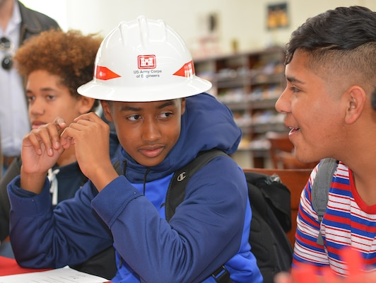 A high school student at John Muir High School in Pasadena, California, tries on a U.S. Army Corps of Engineers hardhat during the school's Engineering and Environmental Science Academy School Exploration Showcase Feb. 14 in Pasadena.