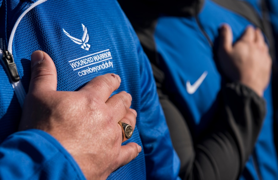 Approximately 150 athletes hold their hands over their hearts during the singing of the national anthem during the 5th Annual Air Force Wounded Warrior Trials opening ceremony at the Warrior Fitness Center on Nellis Air Force Base, Nevada, Feb. 23, 2018. The trials are an adaptive sports event designed to promote the mental and physical well-being of seriously ill and injured military members and veterans. (U.S. Air Force photo by Senior Airman Kevin Tanenbaum)