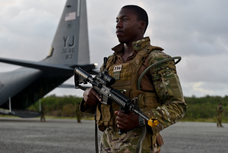 A U.S. Air Force security forces member protects an C-130J Super Hercules during a training scenario at exercise COPE NORTH 18 on Tinian, U.S. Commonwealth of the Northern Marianas Islands, Feb. 20. COPE NORTH enables U.S. and allied forces to train humanitarian assistance/disaster relief operations from austere operating bases, enhancing our capacity and capability to respond in times of crisis. (U.S. Air Force photo by Airman 1st Class Christopher Quail)