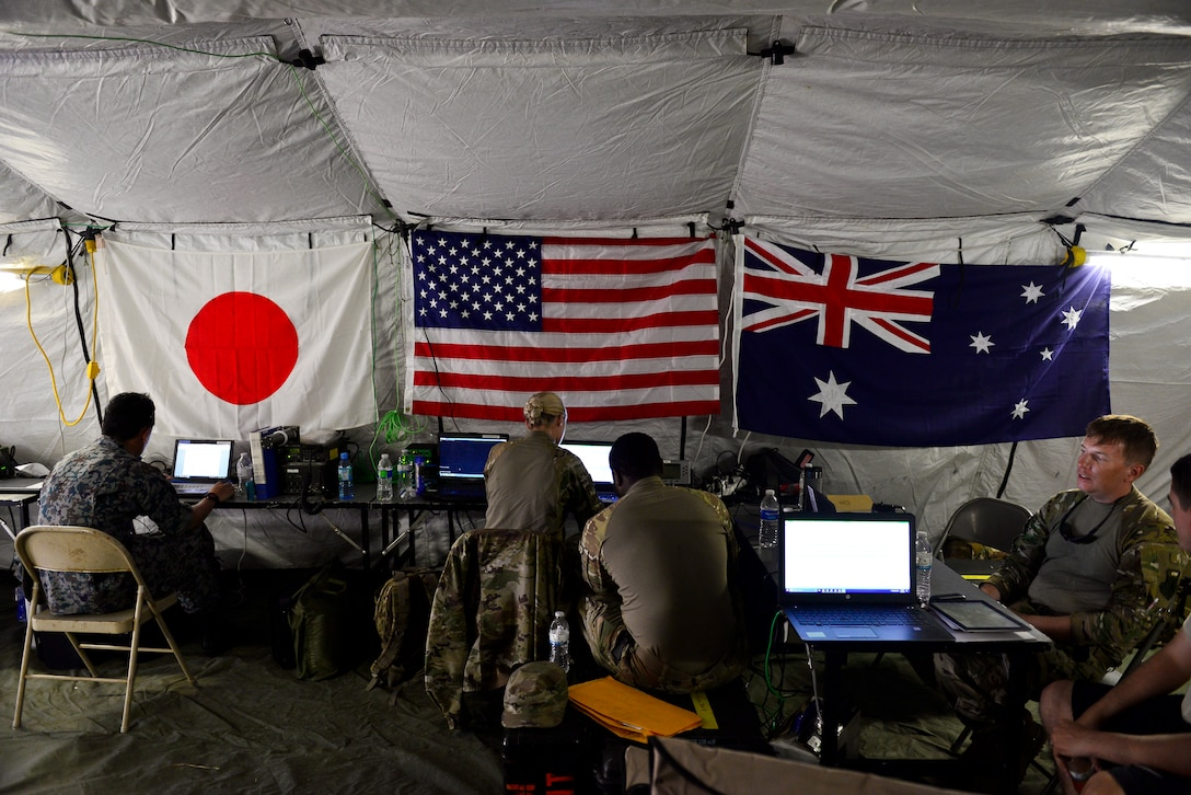U.S. Air Force (USAF), Koku Jieitai (Japan Air Self-Defense) and Royal Australian Air Force (RAAF) members utilize a central command information tent as a HUB to perform logistical re-supply, medical evacuation, troop movement and humanitarian assistance during exercise COPE NORTH 18 at Tinian, U.S. Commonwealth of the Northern Marianas Islands, Feb. 21. Through exercises and engagements during COPE NORTH, USAF, Koku Jieitai and RAAF increase interoperability for humanitarian assistance/disaster relief operations. (U.S. Air Force photo by Airman 1st Class Christopher Quail)