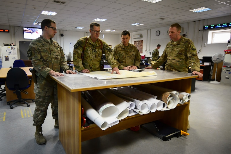 U.S. Air Force Maj. Jon Roe, Lt. Col. Patrick Schuldt, Master Sgt. Kevin Peterson and Maj. Geoffrey Border (left to right), leaders assigned to the 451st Expeditionary Operations Support Squadron, review plans for the continual build-up at Kandahar Airfield, Afghanistan Feb. 22, 2018.