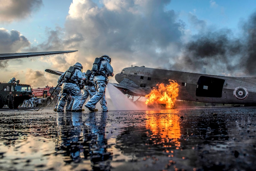 U.S. Marines and Thai navy firefighters work together to extinguish an aircraft fire simulating a crash during aircraft extraction training.