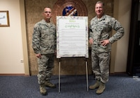 U.S. Air Force Chief Master Sgt. Thomas Daniels, 39th Air Base Wing command chief, and U.S. Air Force Col. David Eaglin, 39th ABW commander, pose with the signed Military Saves Week proclamatio