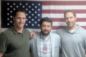 Three men pose for a photograph in front of an American flag in Afghanistan.