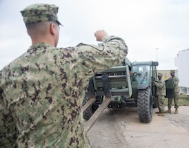 Troops operate an all-terrain forklift vehicle.