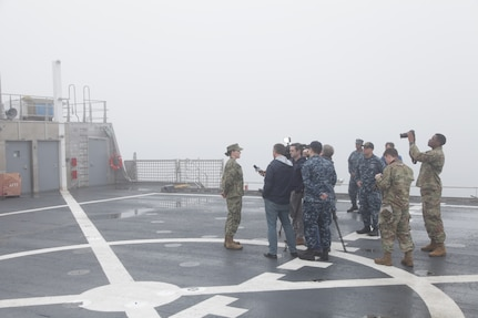 A military member gets interviewed by media aboard USNS Spearhead.