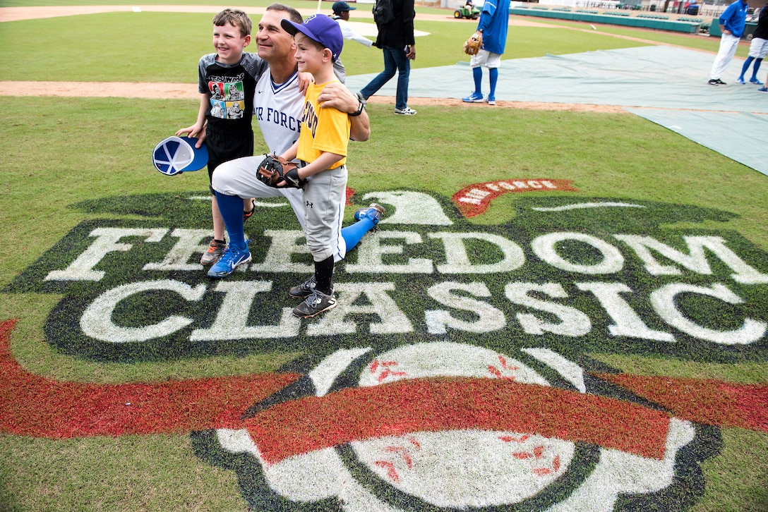 Mike Kazlausky, Air Force Academy baseball head coach, poses with kids for a photo after the kids' baseball clinic taught by coaches and players from the Air Force and Naval Academy baseball teams Feb. 24, 2018, at Grainger Stadium in Kinston, North Carolina. Kazlausky taught the kids how to present themselves during the national anthem and he taught the kids how to properly introduce themselves to people. (U.S. Air Force photo by Tech. Sgt. David W. Carbajal)