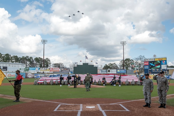 Nearly 50 Airmen attending James C. Binnicker Airman Leadership School at Seymour Johnson Air Force Base, North Carolina, hold the flag Feb. 24, 2018, while four F-15E Strike Eagles fly over Grainger Stadium in Kinston, North Carolina, during the national anthem before game two of the Freedom Classic baseball tournament. The Freedom Classic is the annual tournament between the Air Force and Naval Academy baseball teams, which has been held in Kinston for the past eight years. (U.S. Air Force photo by Tech. Sgt. David W. Carbajal)
