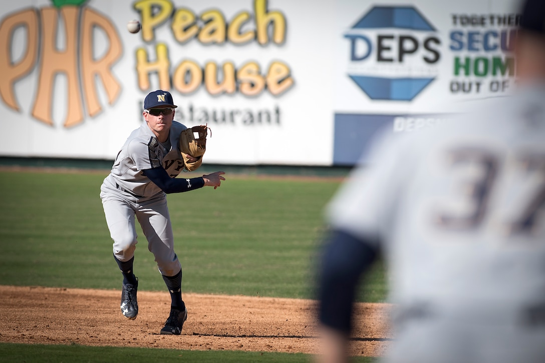 Naval Academy shortstop Michael Coritz throws to Naval Academy first baseman Ben Lowe Feb. 24, 2018, during the Freedom Classic baseball tournament at Grainger Stadium in Kinston, North Carolina. Navy took games one and two of the three-game series against the players from Air Force Academy. (U.S. Air Force photo by Tech. Sgt. David W. Carbajal)