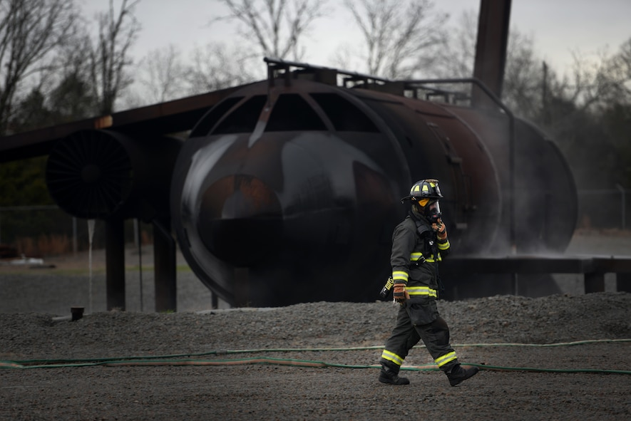A firefighter walks in front of a simulated aircraft while wearing fire protection equipment.