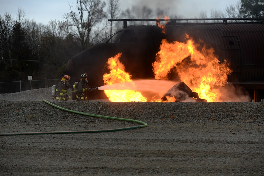 Two firefighters wear fire protective equipment hold a fire hose and use it to put out a fire on a simulated aircraft.