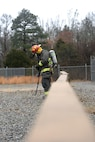 An Airman wearing fire protection equipment is taking off his mask while standing on gravel.