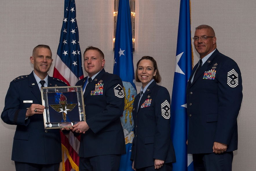 U.S. Air Force Master Sgt. Timothy S. Ogan, First Sergeant assigned to the Air Force Institute of Technology at Wright-Patterson Air Force Base, Ohio, receives the Air Education and Training Command First Sergeant of the Year Award from Lt. Gen. Steve Kwast, Commander of AETC during the AETC 12 Outstanding Airmen of the Year Awards banquet Feb. 22, 2018 in Orlando, Fla. Ogan won Air University First Sergeant of the Year, led18 fellow First Sergeants and 22 committees as President of the First Sergeant Council, as well as completed six credits towards his Master's Degree. (U.S. Air Force photo by Staff Sgt. Kenneth W. Norman)
