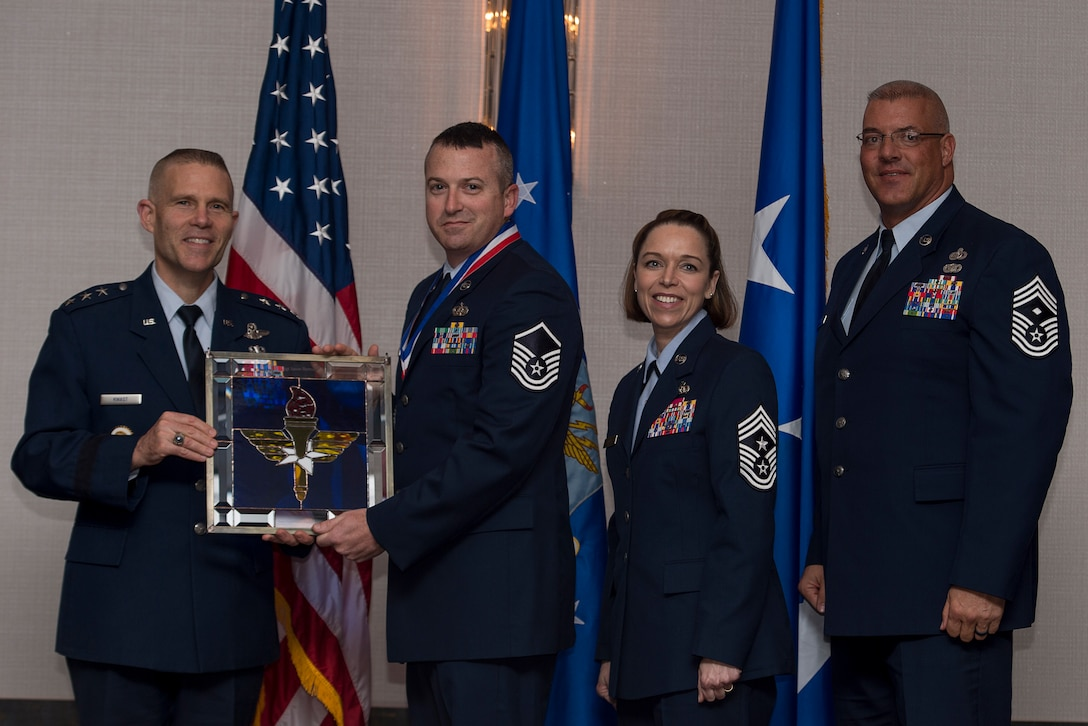 U.S. Air Force Master Sgt. Jason M. Bernich, Superintendent of the base Honor Guard at Keesler Air Force Base, Miss., receives the Chief Master Sergeant of the Air Force Base Honor Guard Program Manager of the Year Award from Lt. Gen. Steve Kwast, Commander of Air Education and Training Command, during the AETC 12 Outstanding Airmen of the Year Awards banquet Feb. 22, 2018 in Orlando, Fla. Bernich shaped AETC's largest Honor Guard area of responsibility, managing 740 honors, 9,500 man-hours and a $70,000 budget, codified funeral requests and liaised with 674 directors and 422 funeral homes, reducing processing time by 101 hours annually, as well as restructured a uniform exchange, outfitting 45 Civil Air Patrol and 122 Junior Reserve Officers' Training Corps cadets. (U.S. Air Force photo by Staff Sgt. Kenneth W. Norman)
