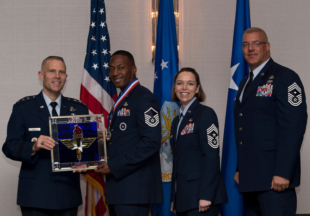 """U.S. Air Force Master Sgt. DaMarcus Forney, Military Training Instructor assigned to the 37th Training Wing at Joint Base San Antonio-Lackland, Texas, receives the Air Education and Training Command MTI of the Year Award from Lt. Gen. Steve Kwast, Commander of AETC during the AETC 12 Outstanding Airmen of the Year Awards banquet, Feb. 22, 2018 in Orlando, Fla. Forney was the 331st Training Squadron's first in parade for four quarters, and led 576 fitness training sessions that resulted in a 99 percent fitness assessment pass rate for his squadron. Forney trained eight flights, garnering four """"BEAST Excellence"""" awards and produced 67 honor graduates, two top graduates, beating the AETC on-time graduate rate by one percent. (U.S. Air Force photo by Staff Sgt. Kenneth W. Norman)"""