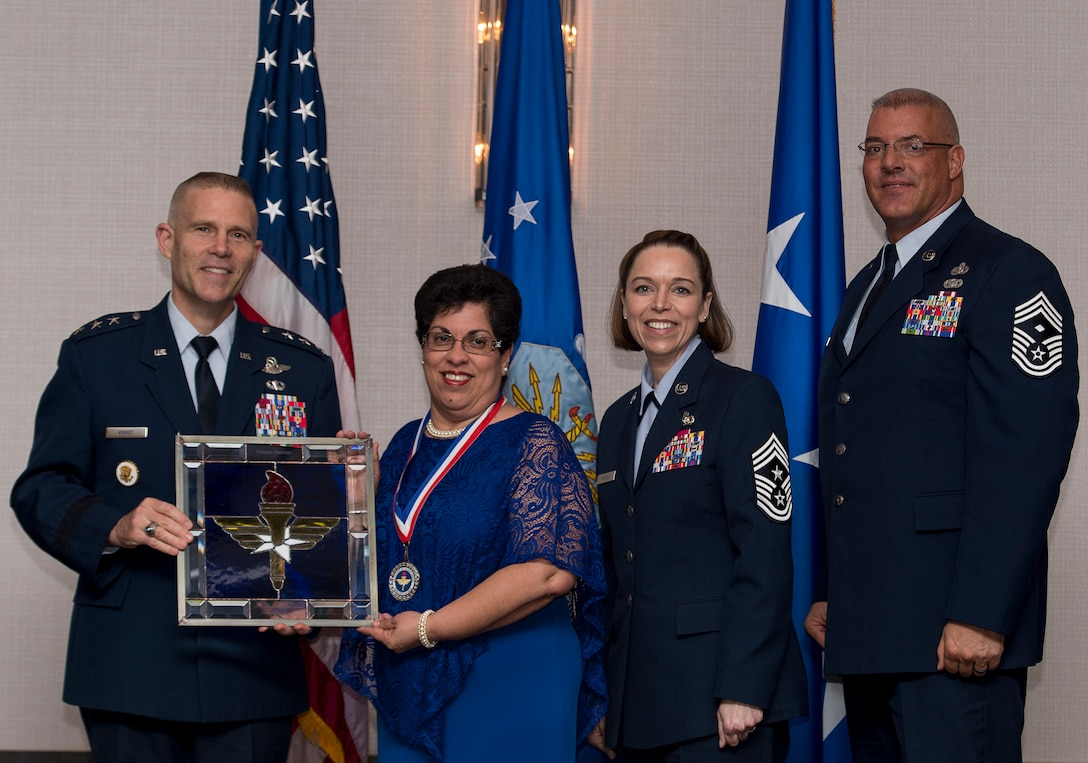 Frances Santiago, Identification Card Section Lead assigned to the 802nd Force Support Squadron at Joint Base San Antonio-Lackland, Texas, receives the 2017 Non-supervisory Civilian of the Year Award from Lt. Gen. Steve Kwast, Commander of AETC, during the AETC 12 Outstanding Airmen of the Year Awards banquet Feb. 22, 2018 in Orlando, Fla. Santiago won the prestigious Depart of Defense, Defense Manpower Data Center High Flyer award, restructured two site operations reducing customer wait times by 50 percent and earning a top 10 rank for office Air Force wide, as well as vetted, educated and terminated 811 Common Access and Identification Cards saving Air Force $8.7 million in erroneous Tricare benefits. (U.S. Air Force photo by Staff Sgt. Kenneth W. Norman)